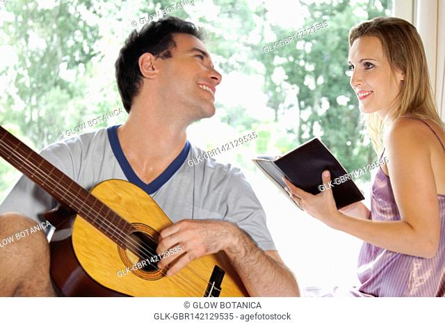 Man playing a guitar with his wife holding a book
