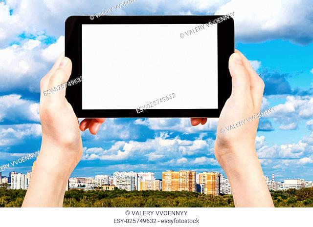 travel concept - hand holds tablet pc with cut out screen and skyline with blue clouds on background