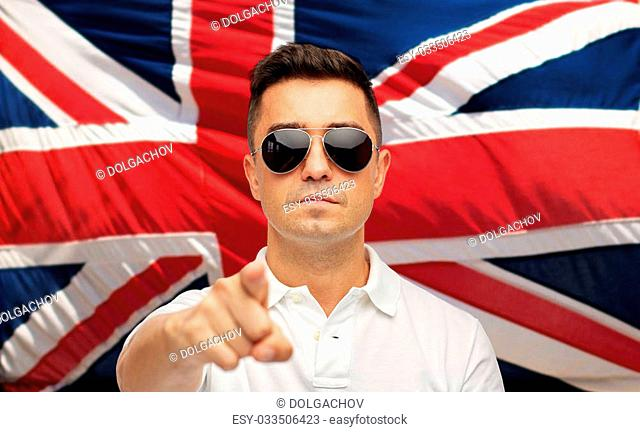summer, accessories, style and people concept - middle aged latin man in white polo t-shirt and sunglasses pointing finger over brittish flag