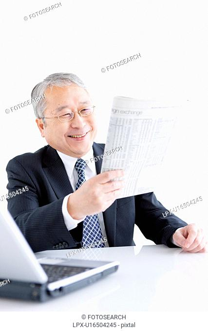 Businessman at Desk Reading Paper
