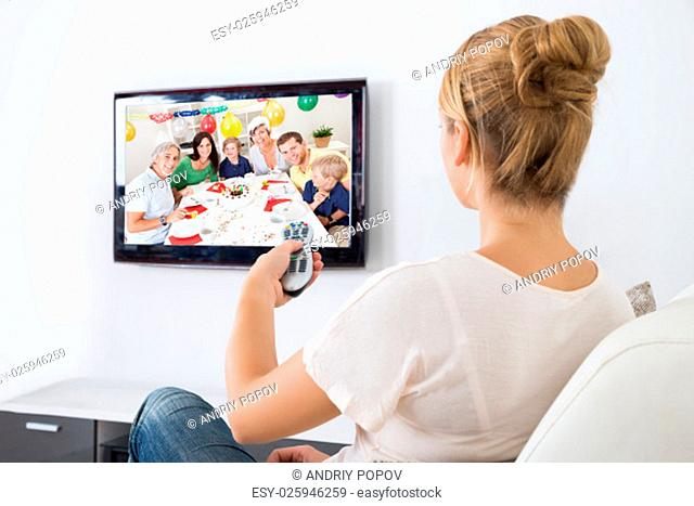 Young woman watching television while sitting on sofa in living room