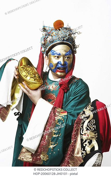 Close-up of a male Chinese opera performer holding a bowl full of gold coins