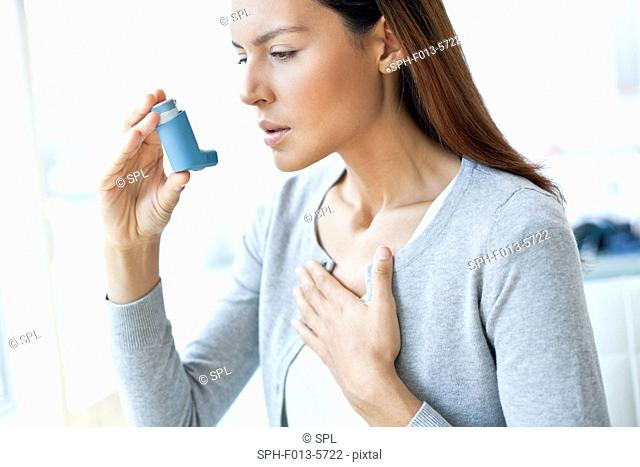 MODEL RELEASED. Young woman using an inhaler and touching her chest