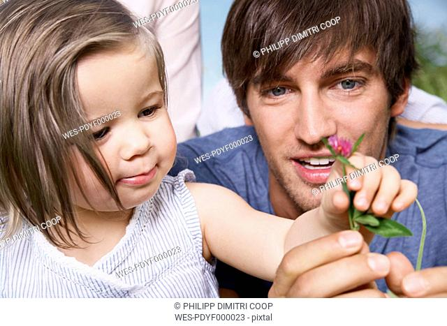 Germany, Cologne, Girl holding flower with parents, close up