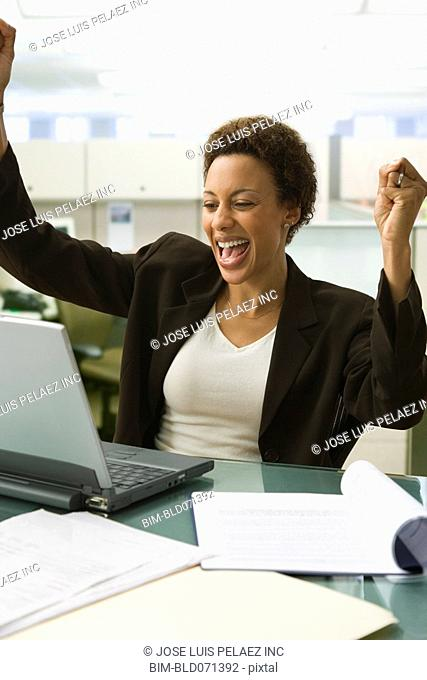 African American businesswoman cheering at desk