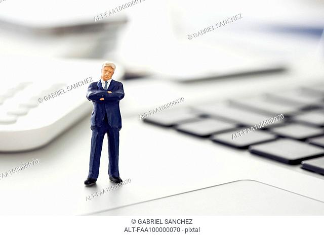 Businessman figurine standing on laptop computer keyboard
