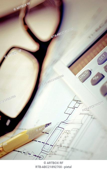 Close-up of eyeglasses and a pencil on a blueprint