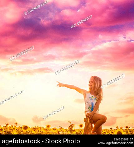 The pretty little girl blonde sits on a wooden ladder among sunflowers and shows her finger in the side