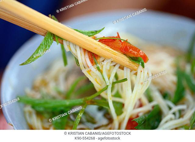 Eating noodle soup as a local speciality with chop sticks on the fresh food market of Hoi An, Vietnam, Southeast Asia