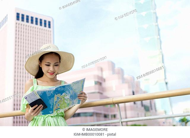 Young woman holding a map and looking down with smile