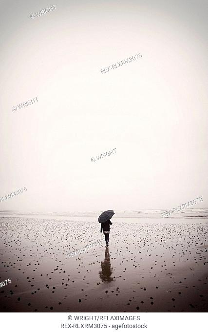 Rear view of teenage girl holding umbrella while walking on wet beach