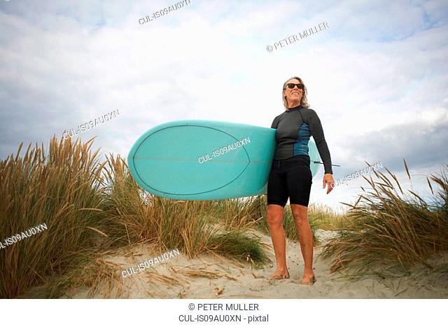 Portrait of senior woman on sand, holding surfboard