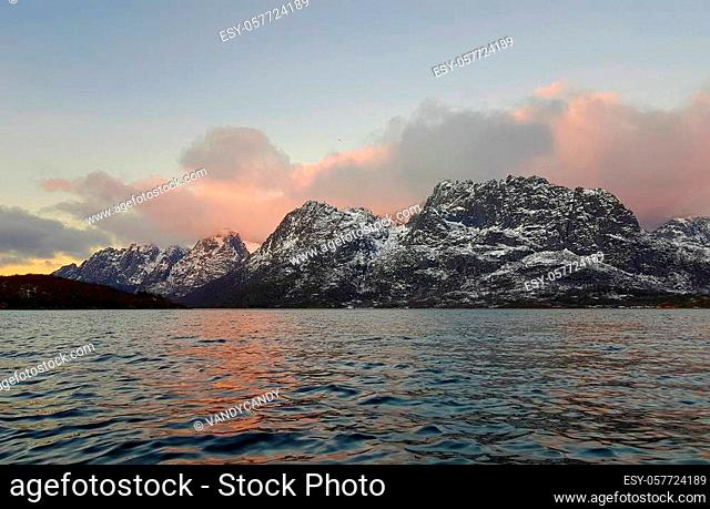 Expansive fjord in the Lofoten Islands surrounded with snowy mountains and a colorful winter sunset. Norway