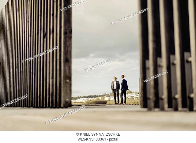 Two businessmen standing on jetty at a lake talking