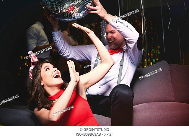 Man and woman fooling around at party, man holding disco ball above woman's head