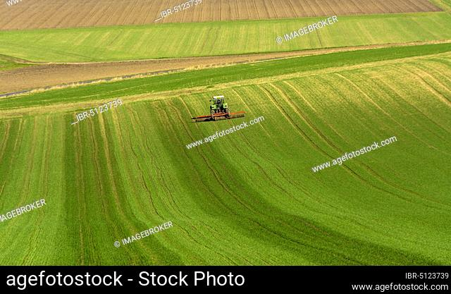 Farmer ploughing his field with tractor, Puy de Dome department, Auvergne-Rhone-Alpes, France, Europe