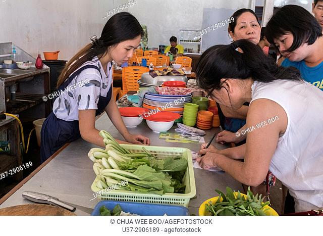 Waitress taking woman's order in Sosok, West Kalimantan, Indonesia