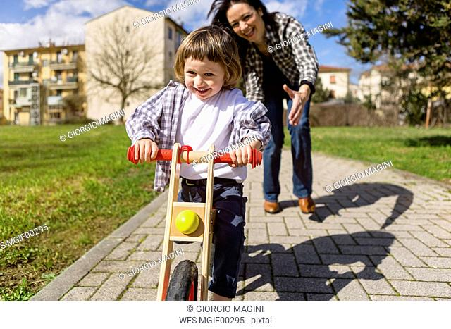 Mother behind happy toddler son with balance bicycle on a path