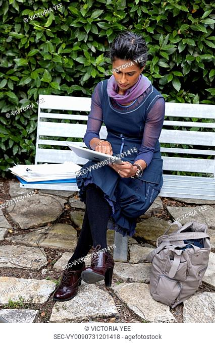 Businesswoman working on tablet outdoors