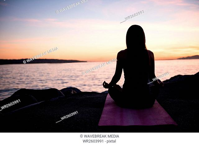 Rear view of woman performing yoga on beach