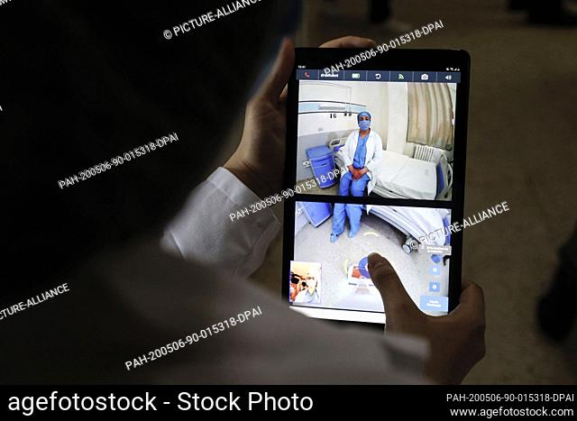 06 May 2020, Tunisia, Ariana: A doctor controls a robot with a mobile as she talks from distance to a coronavirus patient at the Abderrahmen Mami hospital