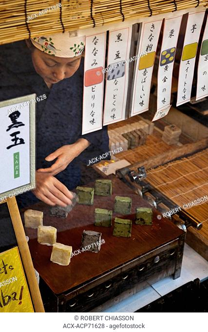 Shopkeeper placing wagashi confectionery on her storefront window display. Ninenzata Street, in Kyoto, Japan