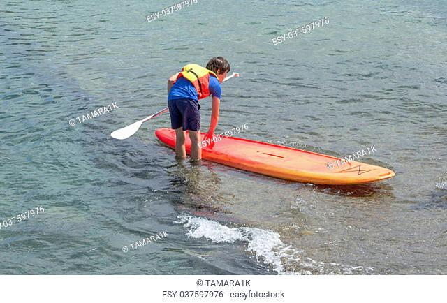 learning stand up and paddle - teenager launching a board
