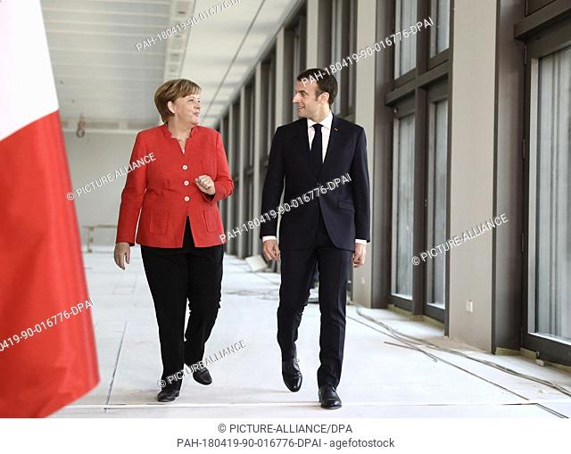 19 April 2018, Germany, Berlin: German Chancellor Angela Merkel (CDU) and French President Emmanuel Macron on their way to a press conference after their visit...