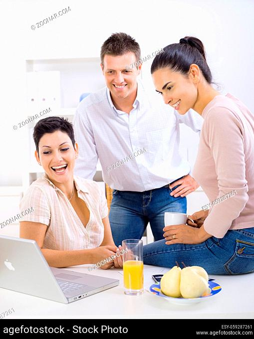 Happy, smiling office workers sitting at desk, looking at laptop computer screen