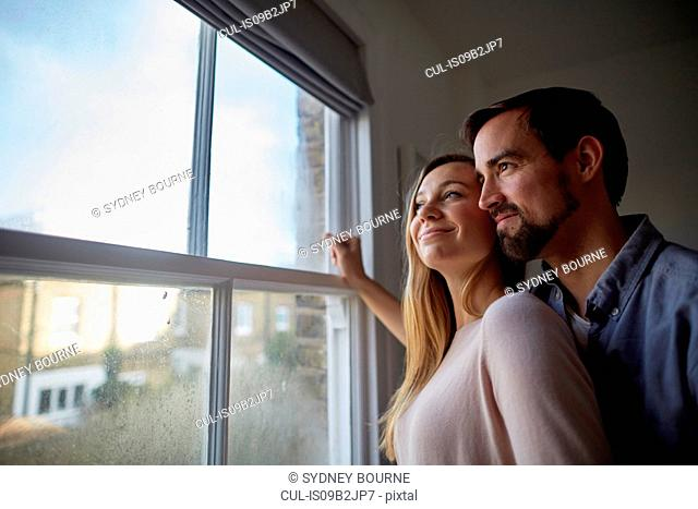 Mid adult couple looking out through bedroom window