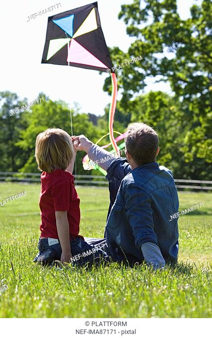 Father and son sitting on grass with kite