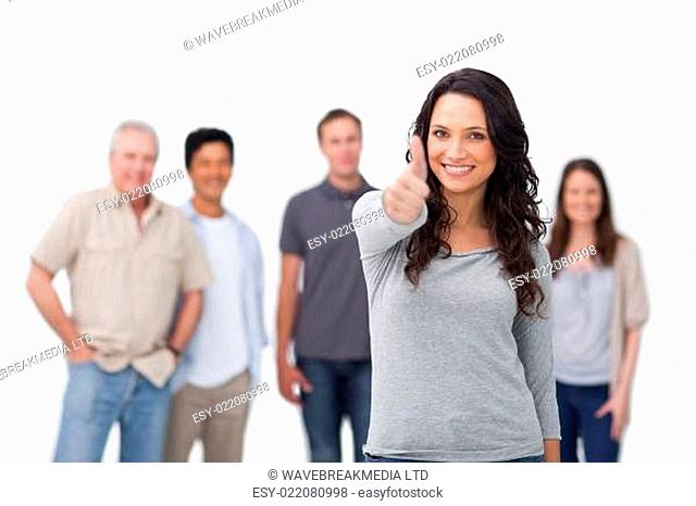 Smiling woman with friends behind her giving thumb up