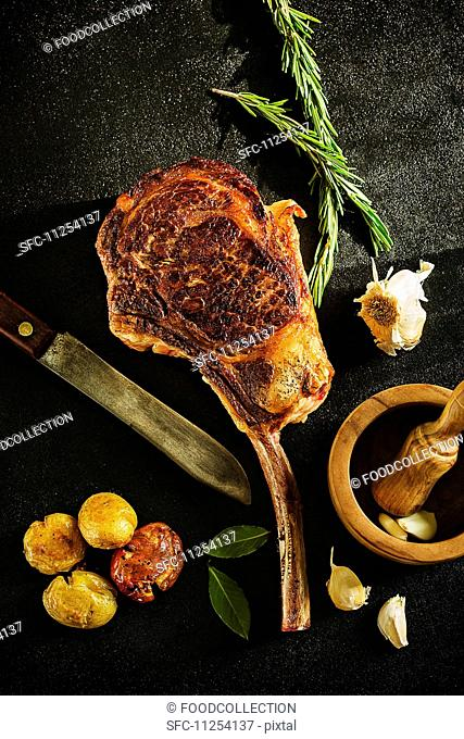 Tomahawk steak served with a baked potato