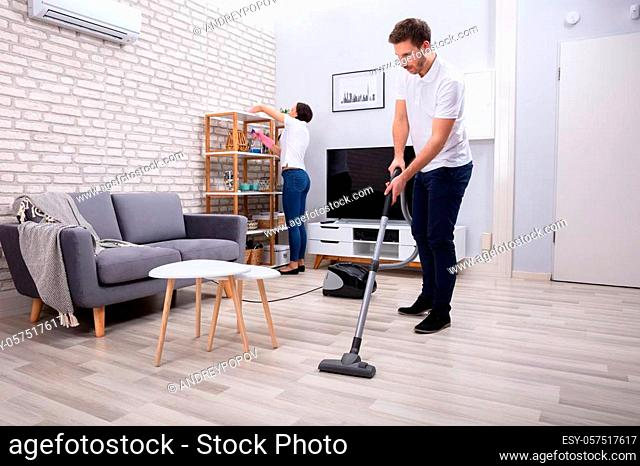 Side View Of Two Persons Cleaning The Shelf And Mopping Floor In The Living Room