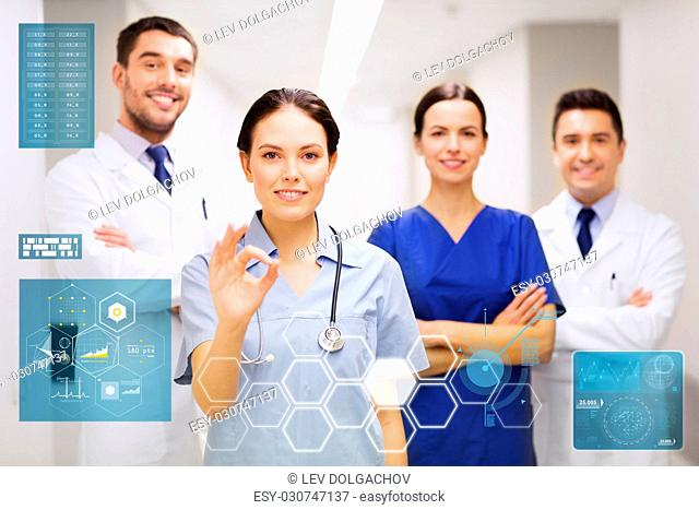 people, healthcare and medicine concept - group of happy medics or doctors at hospital corridor showing ok hand sign