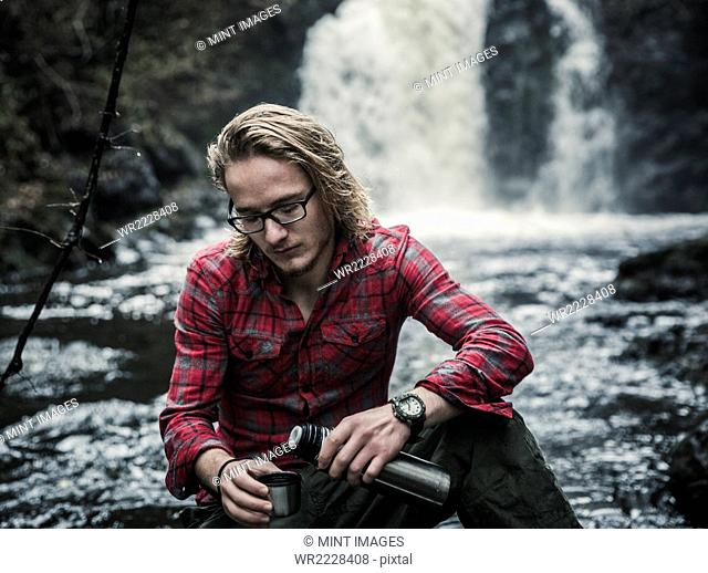 A young man sitting pouring a hot drink from a flask by a fast flowing stream