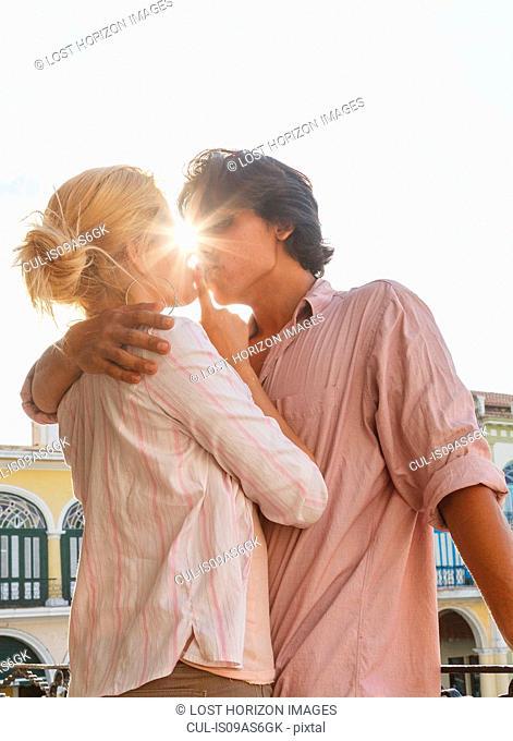 Romantic young couple kissing on restaurant balcony in Plaza Vieja, Havana, Cuba
