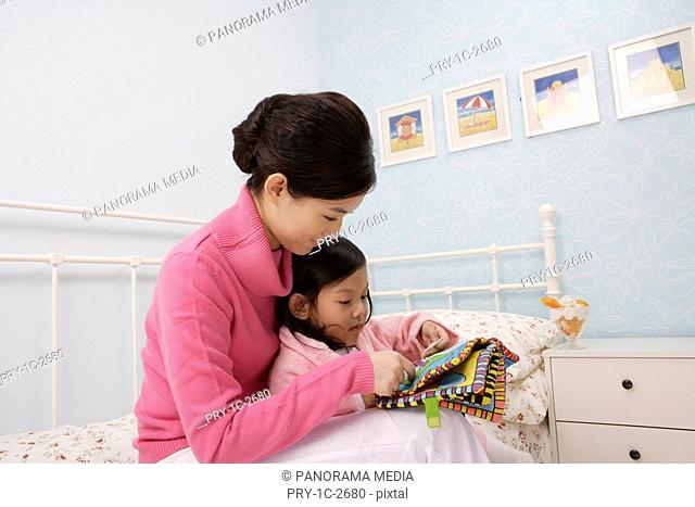 Mother reading out bedtime story to her daughter