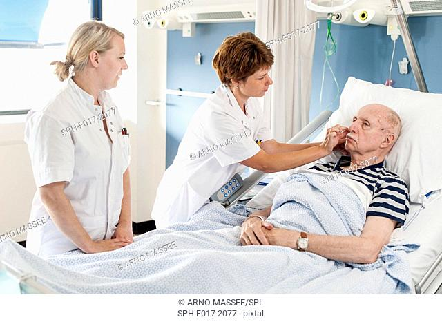 MODEL RELEASED. Senior male patient in hospital bed with female nurses at bedside