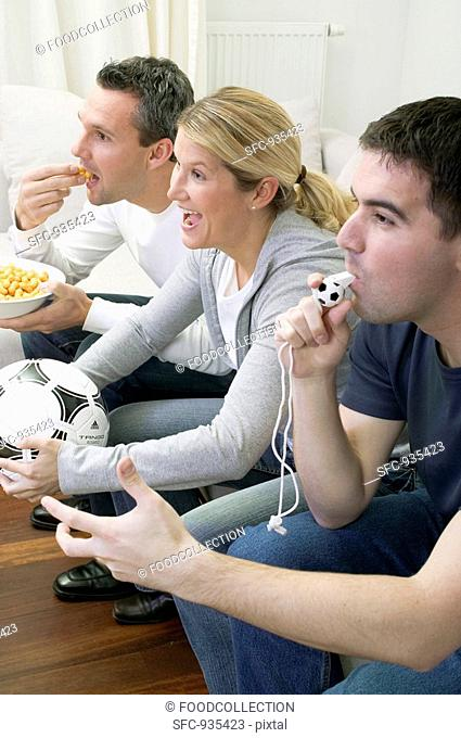 Friends watching TV with referee's whistle, football & crisps