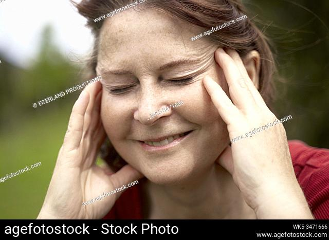 Mature woman in countryside with eyes closed, close up. Bad Tölz, Upper bavaria, Germany