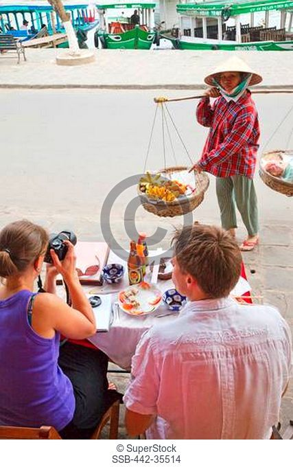 Woman selling fruits to tourist couple, Hoi An, Vietnam