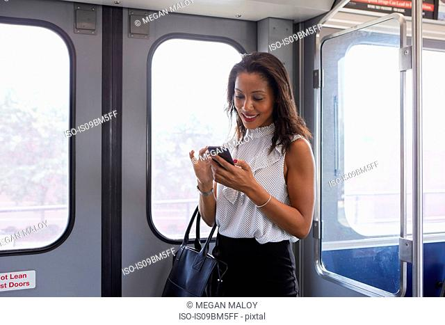 Businesswoman using cellphone in train