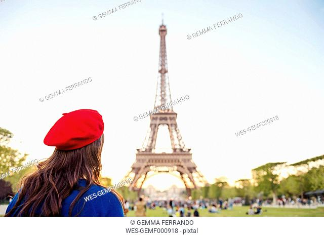 France, Paris, Champ de Mars, back view of woman wearing red beret looking at Eiffel Tower