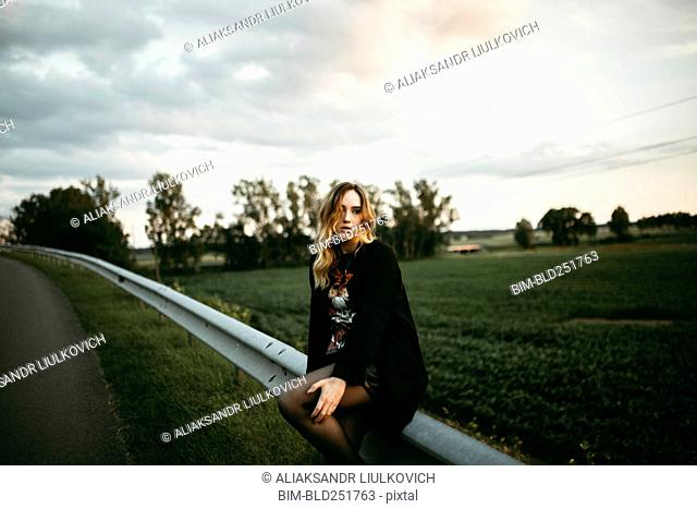 Caucasian woman sitting on guardrail near road
