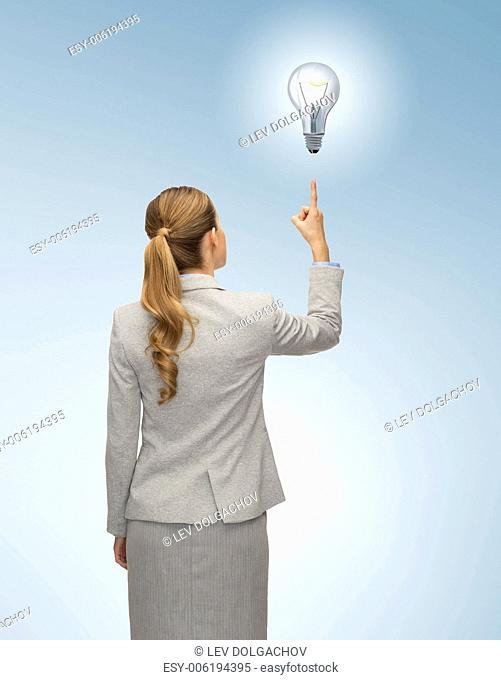 business, education, people and office concept - businesswoman or teacher in suit pointing finger up from back over blue background