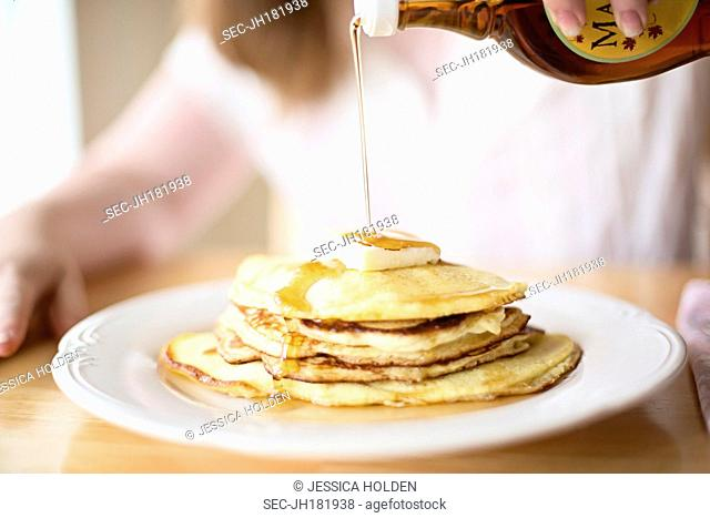 Mid section of teenage girl (13-15) pouring maple syrup over pancakes
