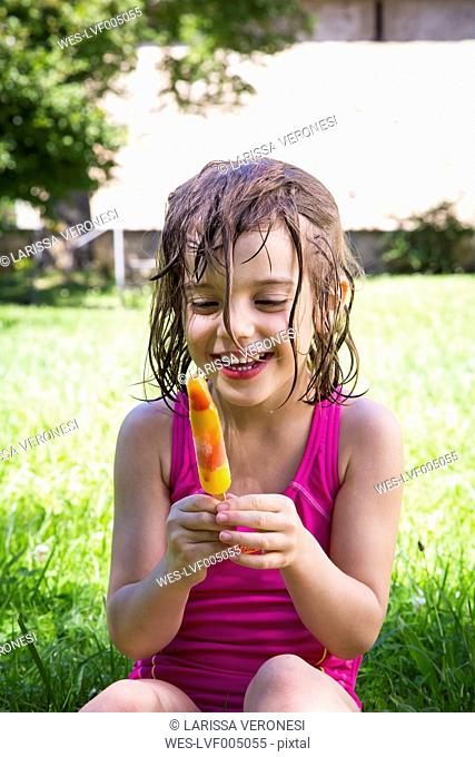 Portrait of happy little girl with wet hair sitting on a meadow with ice lolly