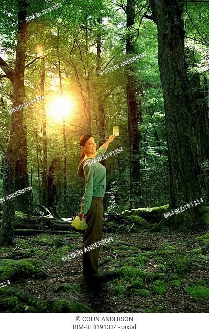 Hispanic woman with color card in forest