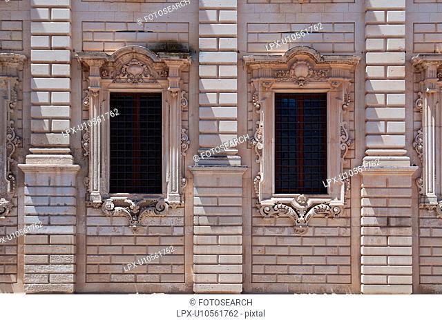 Window detail: ornate Baroque facade of Palazzo del Seminario, ornately carved in Leccese style, grid of metal bars across 2 windows, Lecce, Salento, Puglia